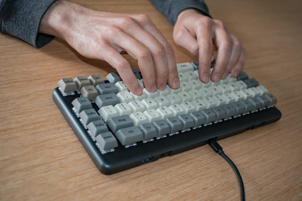 A person typing on the keyboard while their hands stay on the home row.