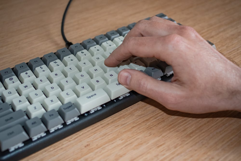A person's right hand resting on the keyboard, their thumb on the right Space bar, other fingers on the home row.