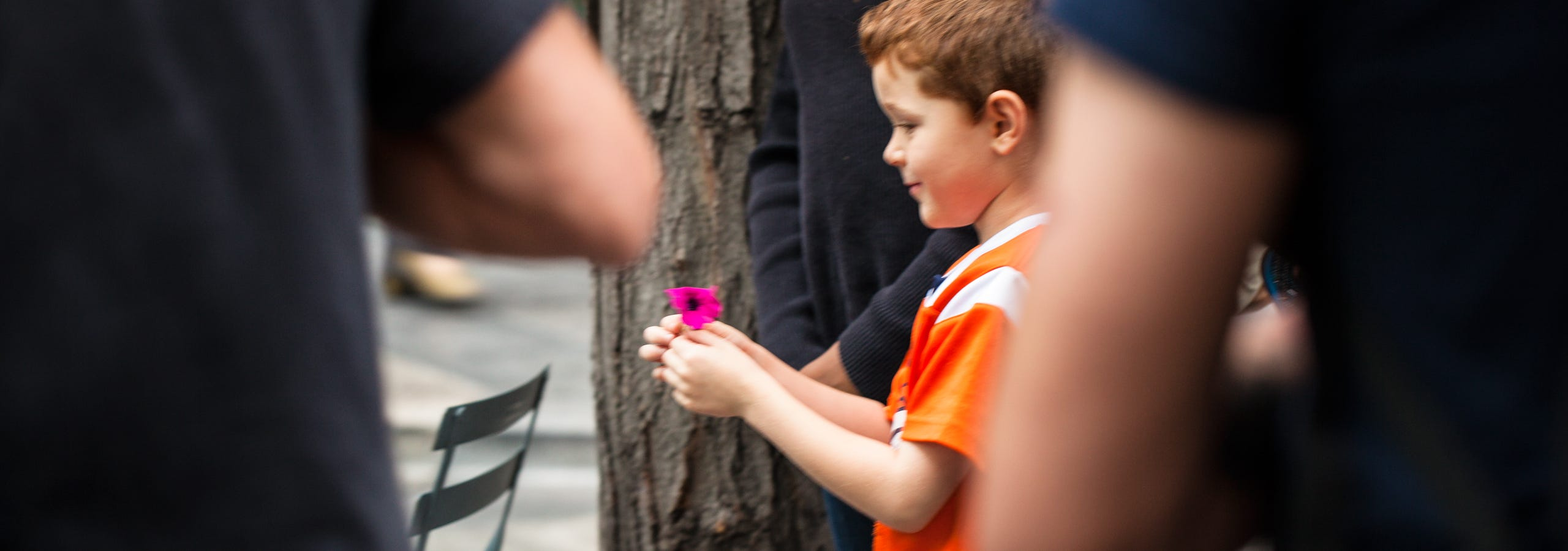Child holding a flower and smiling