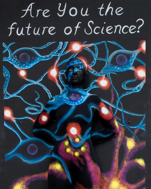 Painted dancer blending into the 'Are you the future of Science?' panel