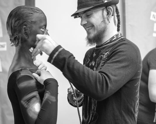 Black and white photo of the dancer getting painted