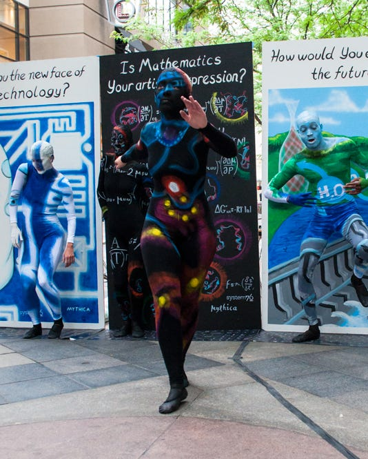 Painted dancer dancing in the street in front of the STEM panels