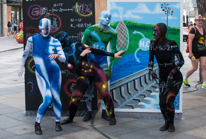 All four painted dancers dancing in front of the Math and Engineering panels